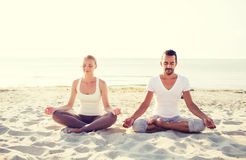 Smiling couple making yoga exercises outdoors Royalty Free Stock Photos