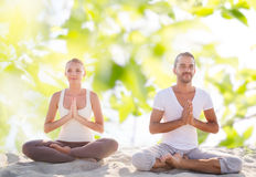 Smiling couple making yoga exercises outdoors Royalty Free Stock Photo
