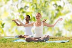 Smiling couple making yoga exercises outdoors Royalty Free Stock Photos