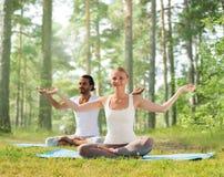 Smiling couple making yoga exercises outdoors Royalty Free Stock Photography