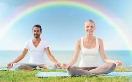 Smiling couple making yoga exercises outdoors. Sport, fitness, yoga and people concept - smiling couple meditating and sitting on mats over sea and rainbow in stock photos