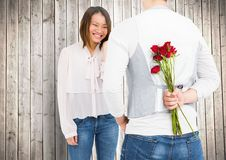 Smiling couple with man hiding roses in his back. Against wooden background Royalty Free Stock Photo