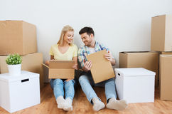 Smiling couple with many boxes moving to new home Stock Image