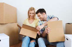 Smiling couple with many boxes moving to new home Stock Photos