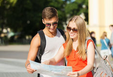 Smiling couple with map and backpack in city Royalty Free Stock Photo