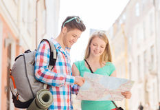 Smiling couple with map and backpack in city Royalty Free Stock Images
