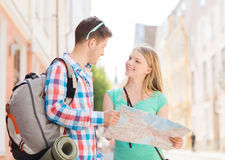 Smiling couple with map and backpack in city Stock Photos