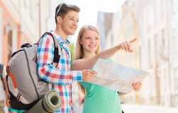 Smiling couple with map and backpack in city Royalty Free Stock Photography