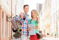 Smiling couple with map and backpack in city Stock Images
