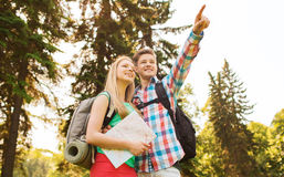 Smiling couple with map and backpack in nature Stock Image