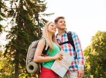 Smiling couple with map and backpack in nature Royalty Free Stock Photography