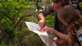 Smiling couple with map on a hike in the countryside stock video