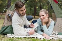 Smiling couple with a map lying in tent Royalty Free Stock Photos