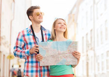 Smiling couple with map and photo camera in city Royalty Free Stock Photos