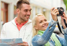 Smiling couple with map and photocamera in city Stock Images