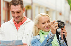 Smiling couple with map and photocamera in city Royalty Free Stock Photo