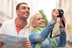 Smiling couple with map and photocamera in city Royalty Free Stock Photos