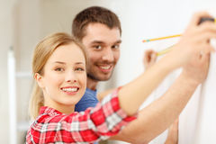 Smiling couple measuring wall Royalty Free Stock Photo