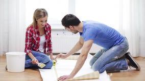 Smiling couple measuring wallpaper stock video