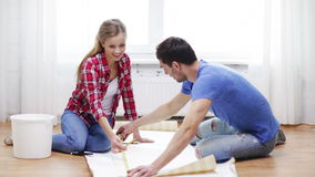 Smiling couple measuring wallpaper Stock Image
