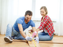 Smiling couple measuring wood flooring Stock Photography