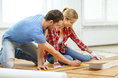 Smiling couple measuring wood flooring Royalty Free Stock Images