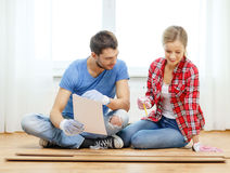 Smiling couple measuring wood flooring Royalty Free Stock Image