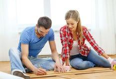 Smiling couple measuring wood flooring. Repair, building and home concept - smiling couple measuring wood flooring Royalty Free Stock Photos