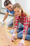 Smiling couple measuring wood flooring Stock Photos