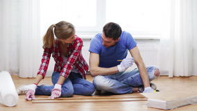 Smiling couple measuring wood flooring Stock Images