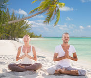 Smiling couple meditating on tropical beach Royalty Free Stock Photo