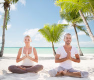 Smiling couple meditating on tropical beach Royalty Free Stock Photography