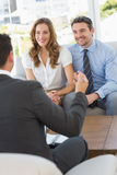 Smiling couple in meeting with a financial adviser Stock Images