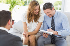 Smiling couple in meeting with a financial adviser Royalty Free Stock Photos