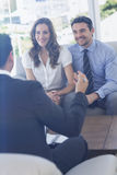 Smiling couple in meeting with a financial adviser. Smiling young couple in meeting with a financial adviser at home Royalty Free Stock Photography