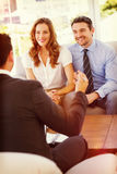 Smiling couple in meeting with a financial adviser. Smiling young couple in meeting with a financial adviser at home Stock Photography