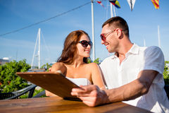 Smiling couple with menu at cafe Royalty Free Stock Image