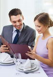 Smiling couple with menu at restaurant. Restaurant, couple and holiday concept - smiling couple with menu at restaurant Royalty Free Stock Photo