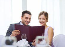 Smiling couple with menu at restaurant Royalty Free Stock Photos