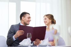 Smiling couple with menu at restaurant Stock Photography