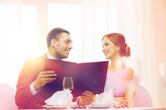 Smiling couple with menu at restaurant. Restaurant, couple and holiday concept - smiling couple with menu at restaurant Stock Photo