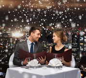 Smiling couple with menus at restaurant Royalty Free Stock Photo