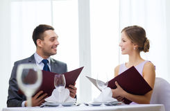 Smiling couple with menus at restaurant Stock Image