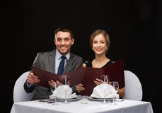 Smiling couple with menus at restaurant Royalty Free Stock Image