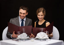 Smiling couple with menus at restaurant Royalty Free Stock Photography