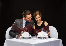 Smiling couple with menus at restaurant Stock Photography