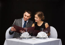 Smiling couple with menus at restaurant Royalty Free Stock Photos