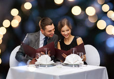 Smiling couple with menus at restaurant Stock Photo