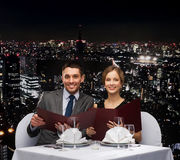Smiling couple with menus at restaurant Royalty Free Stock Images