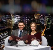 Smiling couple with menus at restaurant Stock Images